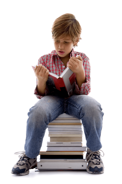 Boy sitting on pile of books and reading